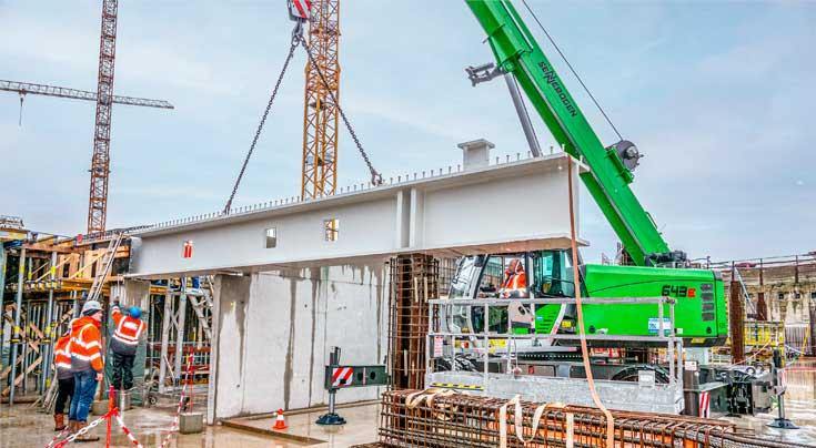 Bei der Platzierung der knapp 14 t schweren Stahlbetonträger ist höchste Präzision gefordert. Fotos: Sennebogen